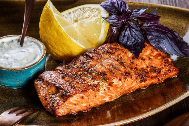 Os salmões cozidos enfaixam com molho, manjericão e limão de queijo na placa no fundo de madeira imagens de stock