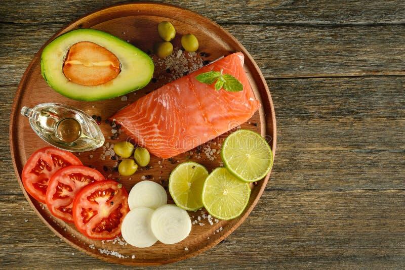 Os salmões vermelhos da carne pescam, tomates, especiarias, limão, azeitonas verdes na mesa de cozinha de madeira imagens de stock royalty free
