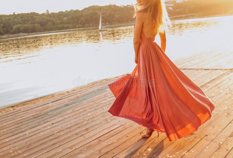 Os saltos bonitos dos vestidos das meninas encalham o lazer do beira-mar imagem de stock royalty free