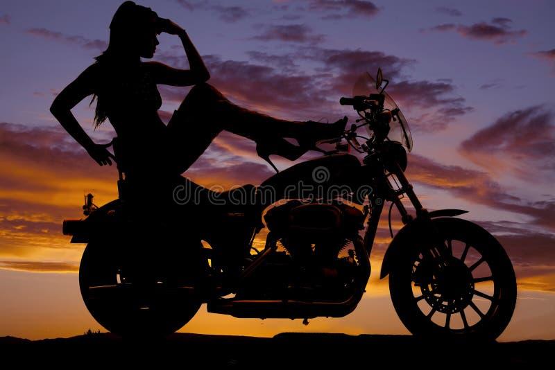Os saltos da motocicleta da mulher da silhueta levantam a cabeça da mão imagens de stock royalty free