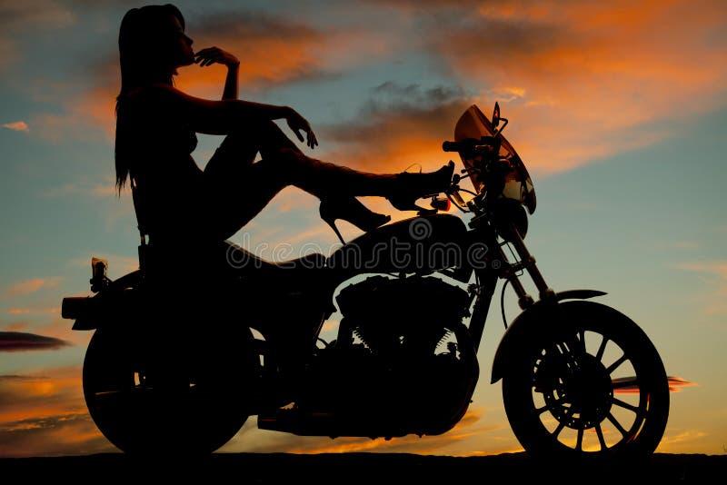 Os saltos da motocicleta da mulher da silhueta levantam o queixo da mão imagem de stock royalty free