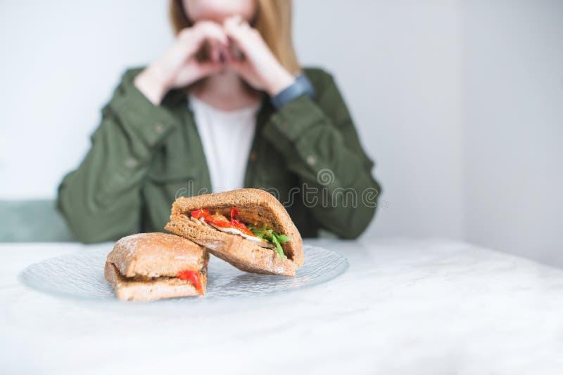 Os sanduíches apetitosos encontram-se na tabela em uma placa no fundo de uma mulher Os pratos da mulher com sanduíches fotos de stock