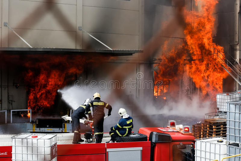 Os sapadores-bombeiros esforçam-se para extinguir o fogo que estoirou na fotografia de stock