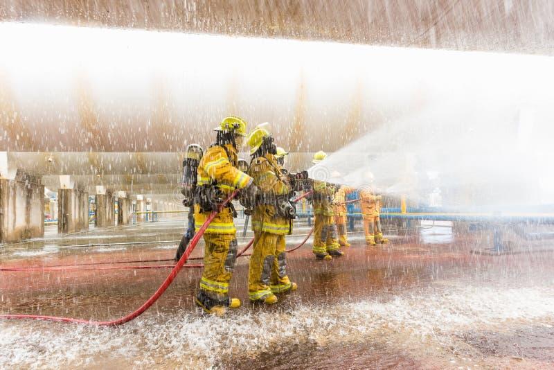 Os sapadores-bombeiros que treinam, primeiro plano são gota do springer da água imagens de stock