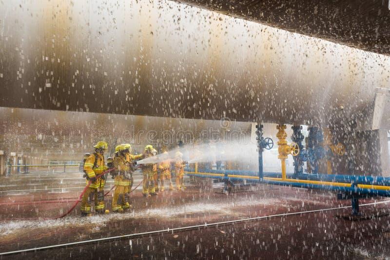 Os sapadores-bombeiros que treinam, primeiro plano são gota do springer da água imagens de stock royalty free