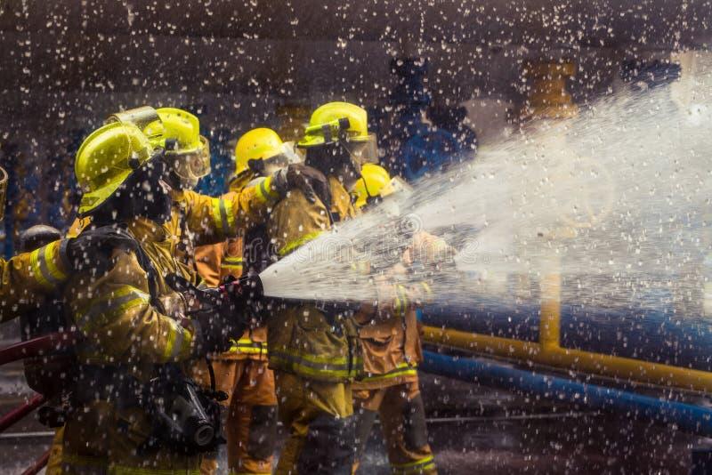 Os sapadores-bombeiros que treinam, primeiro plano são gota do springer da água, Sel fotografia de stock