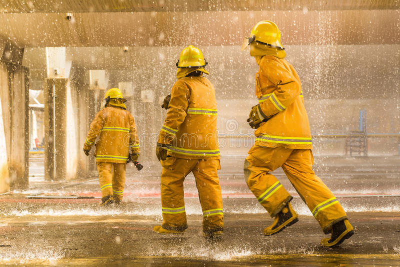 Os sapadores-bombeiros que treinam, primeiro plano são gota do springer da água, Sel fotos de stock