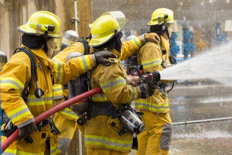 Os sapadores-bombeiros que treinam, primeiro plano são gota do springer da água, Sel imagens de stock