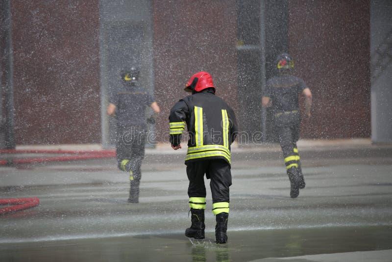 Os sapadores-bombeiros sob espirram da água foto de stock royalty free