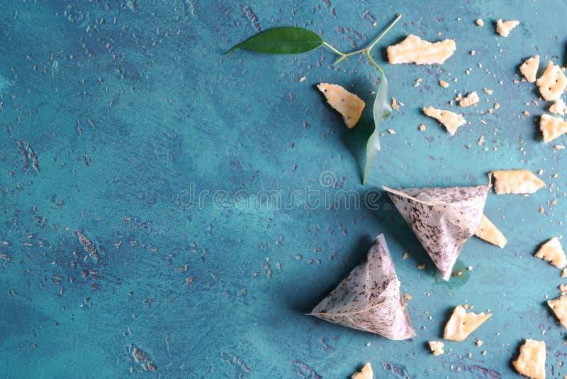 Os saquinhos de chá e a cookie usados desintegram-se na tabela fotos de stock