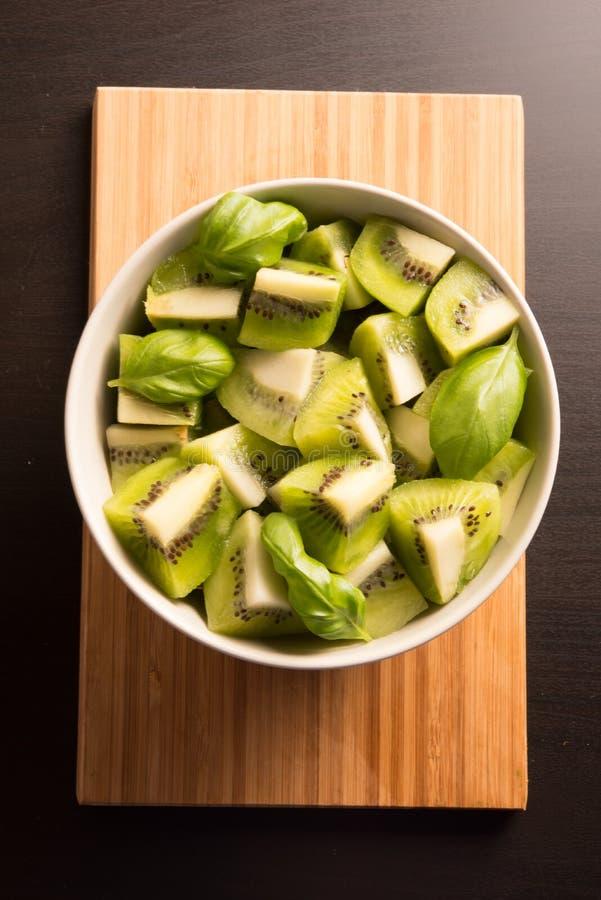 Os segmentos cortados do fruto de quivi com manjericão saem em uma bacia redonda imagem de stock royalty free