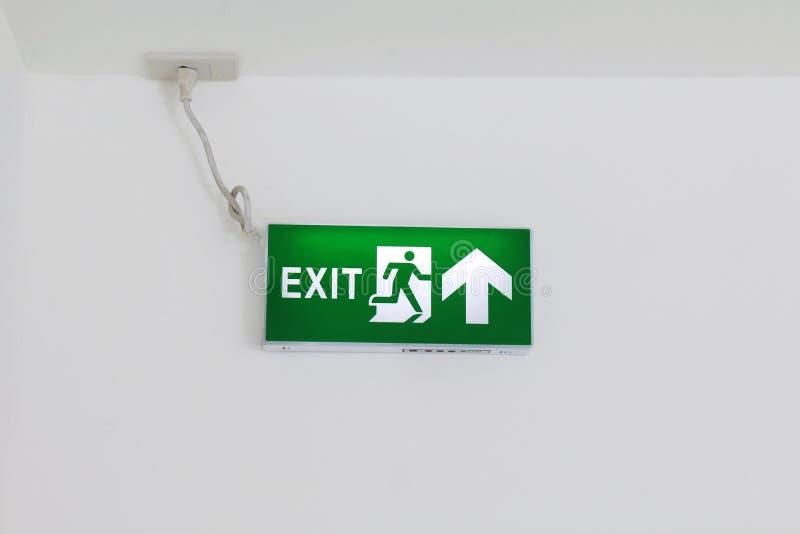 Os sinais da saída de emergência, verde do escape de fogo, seta assinam na parede branca, emergência dos sinais, sinais da caixa  fotografia de stock royalty free