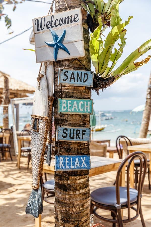 Os sinais de madeira BOA VINDA, AREIA, PRAIA, RESSACA, RELAXAM e um peixe de madeira em uma árvore em um café do lado da praia em foto de stock royalty free