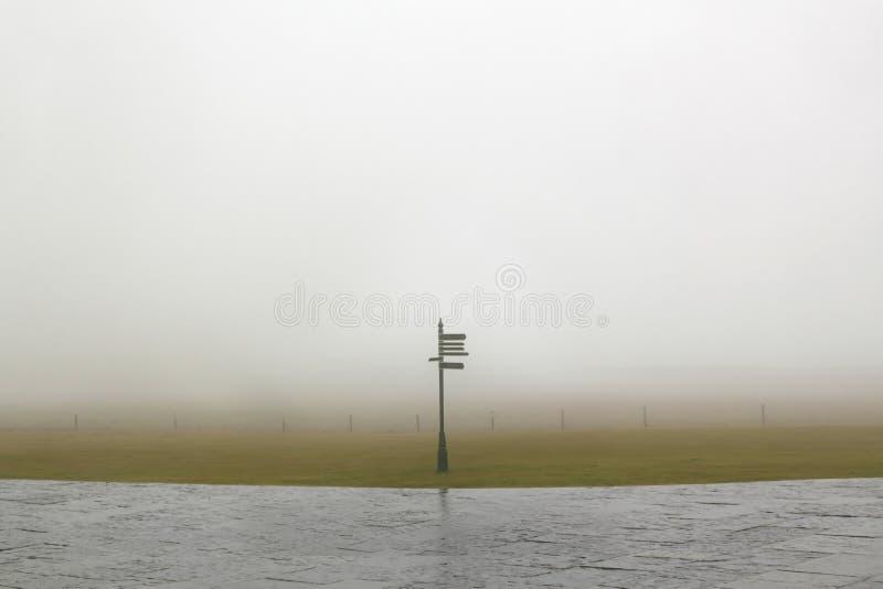 Os sinais de sentido do turista sinalizam em um dia nevoento fotografia de stock royalty free