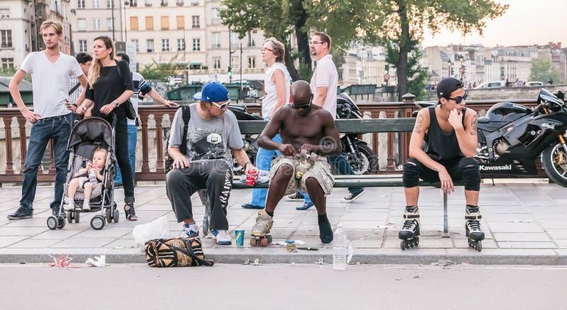 Os skateres dos homens novos sentam-se no banco e no prepa da ponte pedestre de Paris imagem de stock royalty free