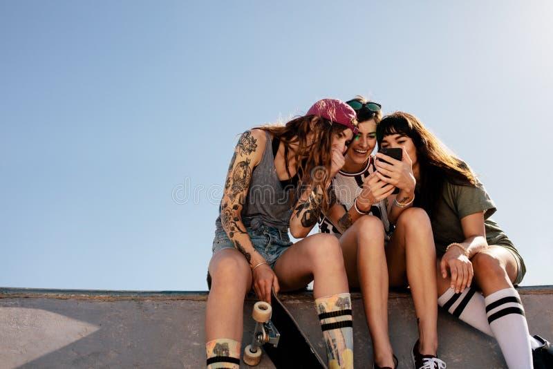Os skateres fêmeas que sentam-se no patim estacionam usando o smartphone fotos de stock
