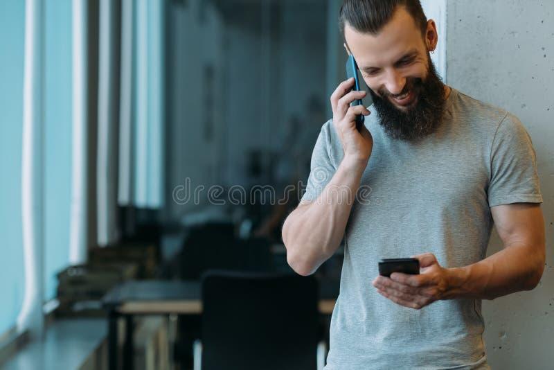 Os smartphones do homem da gestão do projeto falam o escritório fotos de stock royalty free