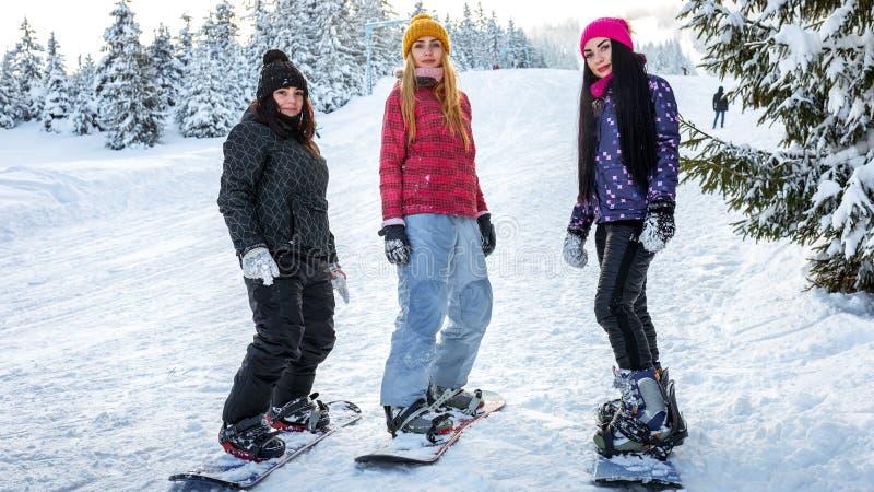 Os snowboarders das meninas estão nas placas nas inclinações do esqui imagens de stock royalty free