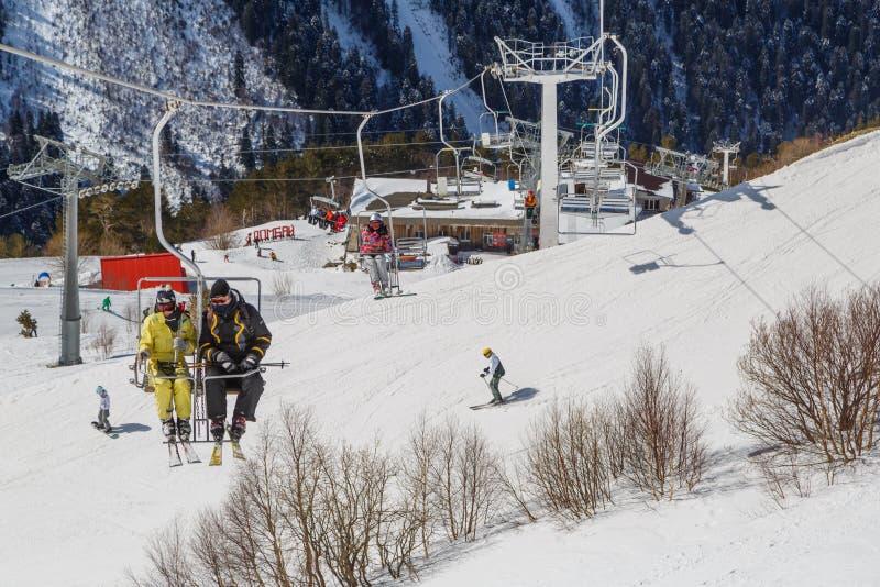 Os Snowboarders e os esquiadores aumentam no elevador de cadeira na montanha imagem de stock