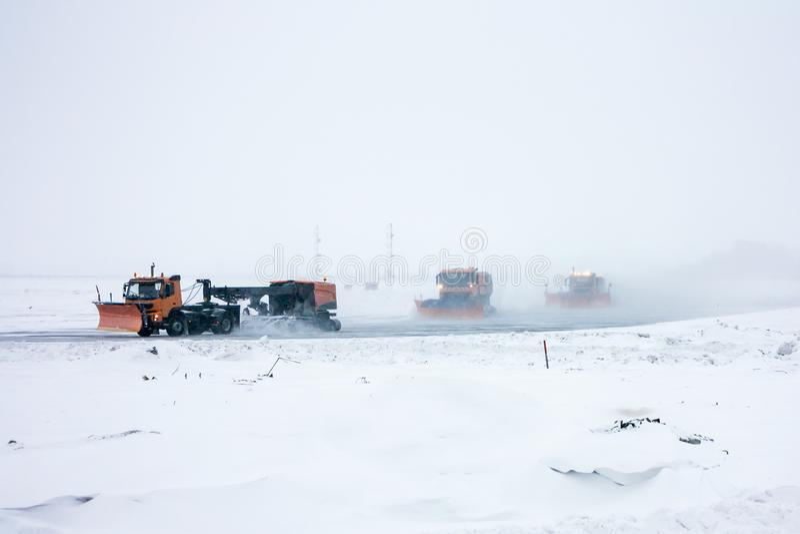 Os Snowplows limpam o taxiway imagem de stock