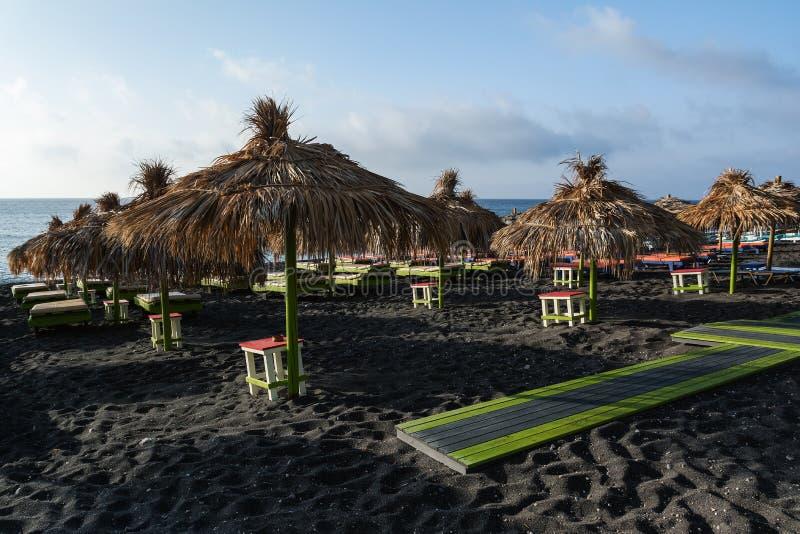 Os solários e os guarda-chuvas da palha em Perissa encalham, ilha de Santorini, Grécia fotos de stock