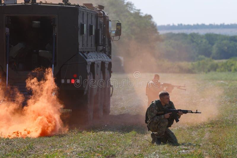 Os soldados das forças especiais sentam-se com armas em torno de um carro blindado fotos de stock