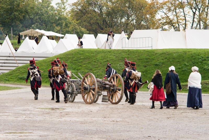 Os soldados de Napoleão e suas mulheres estão marchando a um acampamento militar Base de Napoleão com barracas brancas imagem de stock
