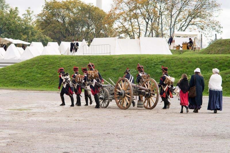 Os soldados de Napoleão e suas mulheres estão marchando a um acampamento militar Base de Napoleão com barracas brancas foto de stock royalty free