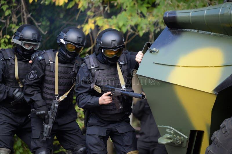 Os soldados de Special Forces da guarda nacional conduzem uma operação sob a tampa de um veículo blindado de transporte de pessoa fotografia de stock