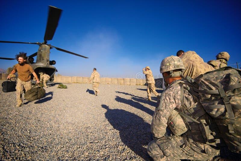 Os soldados embarcam um helicóptero de Chinook imagens de stock