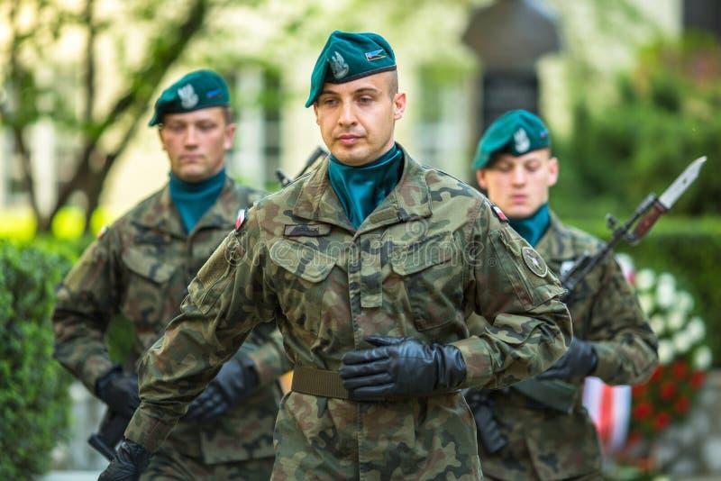 Os soldados poloneses na cerimônia da colocação florescem ao monumento a Hugo Kollataj durante o nacional e o feriado do polonês  imagens de stock royalty free