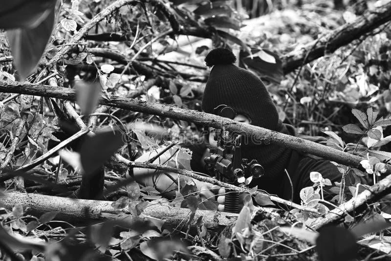 Os soldados que apontam o alvo e que mantêm seus rifles escondidos ambushed, camuflagem do atirador furtivo do exército na flores imagem de stock royalty free