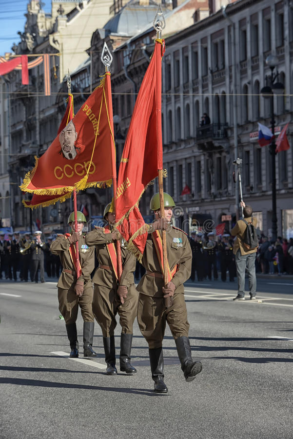 Os soldados sob a forma da segunda guerra mundial com as bandeiras soviéticas em suas mãos na vitória desfilam fotografia de stock royalty free