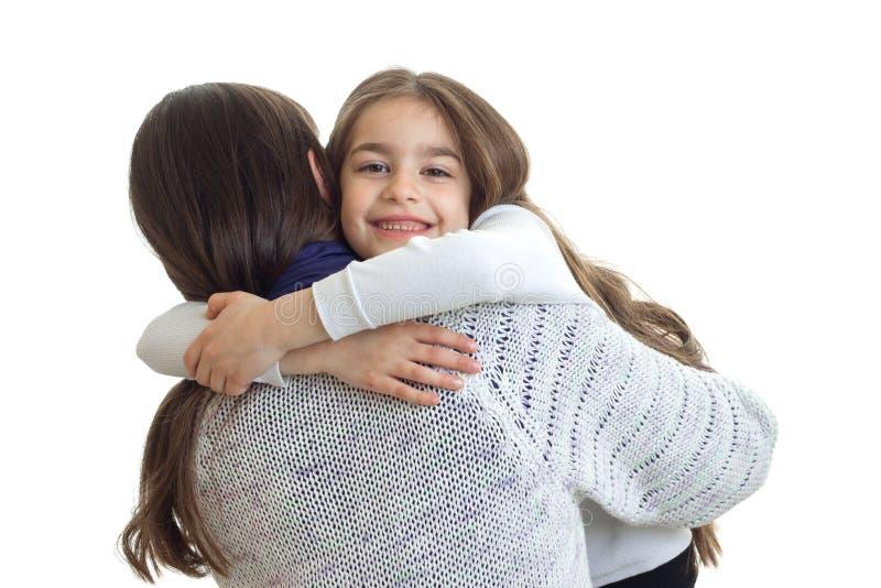 Os sorrisos da menina e abraçam seu close-up da mãe imagem de stock royalty free