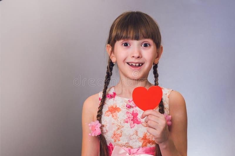 Os sorrisos da menina e o coração disponivel das posses fotos de stock royalty free