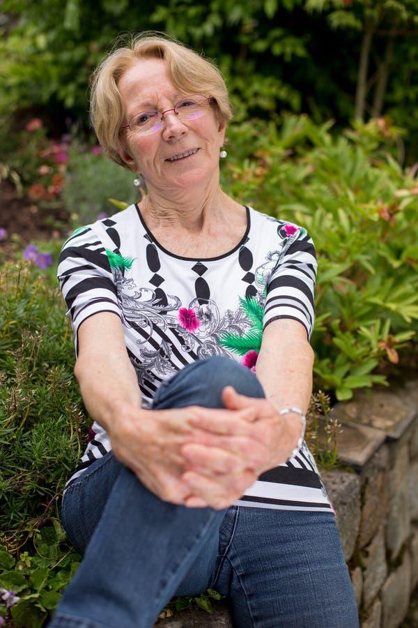 Os sorrisos idosos agradáveis de uma mulher sentam-se no jardim e sorriem-se na câmera que dobra um joelho e inclinar-se nela sen foto de stock royalty free