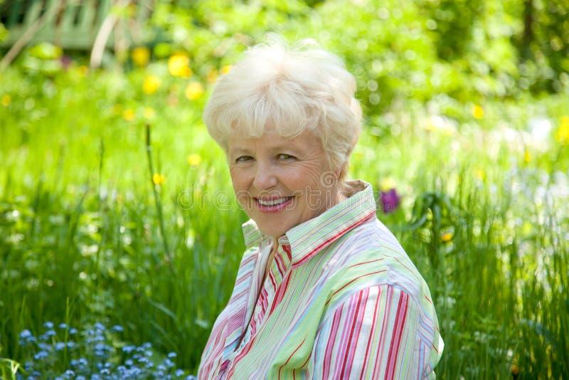 Os sorrisos idosos da mulher fotografia de stock royalty free