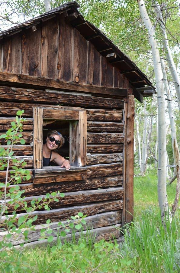 Os sorrisos urbanos do explorador da mulher através de uma janela quebrada em uma cabana rústica de madeira velha nos mineiros de foto de stock