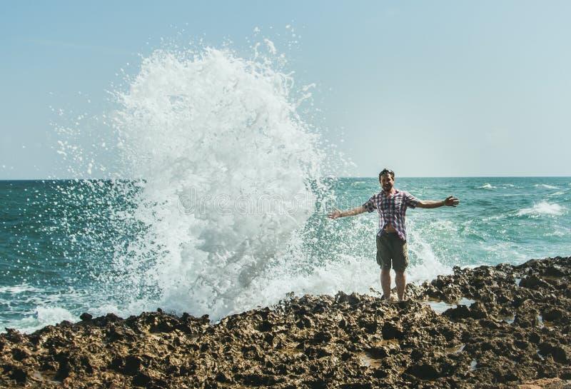 Os suportes de um homem novo na costa no pulverizador de deixar de funcionar acenam fotografia de stock royalty free