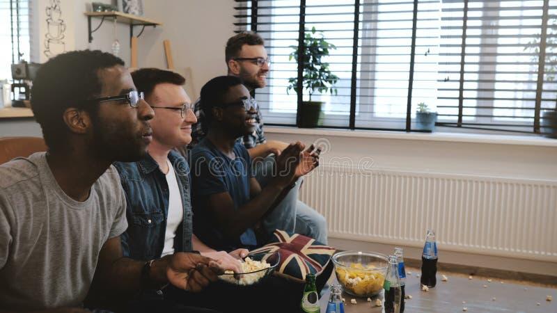 Os suportes masculinos da raça misturada olham esportes na tevê 4K Os fãs comemoram a vitória do objetivo que guarda o coxim brit imagem de stock