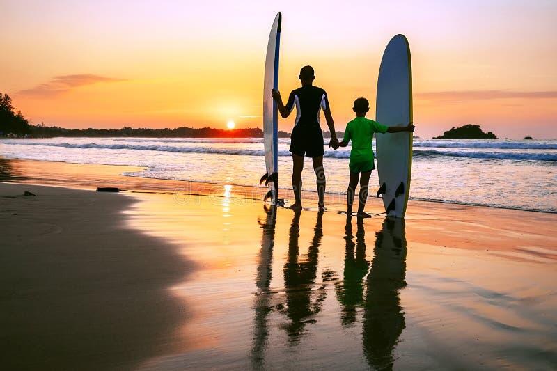 Os surfistas do pai e do filho encontram um por do sol na praia do oceano foto de stock