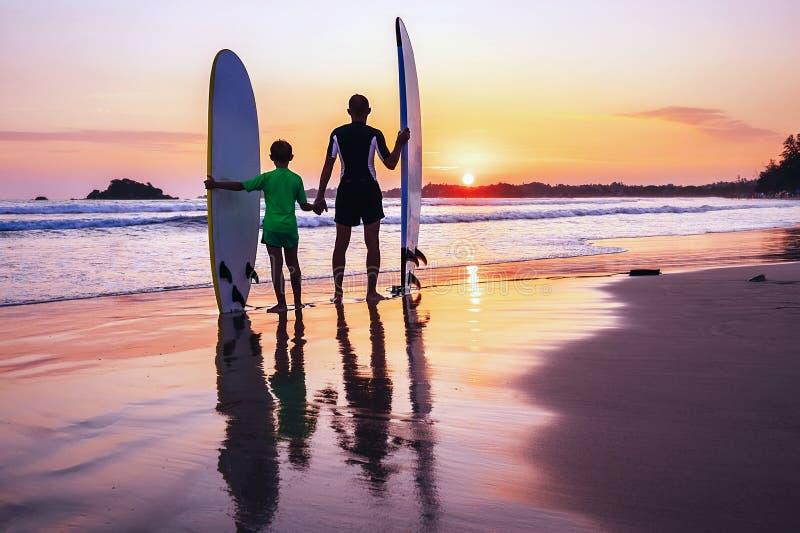 Os surfistas do pai e do filho encontram um por do sol na praia do oceano imagens de stock