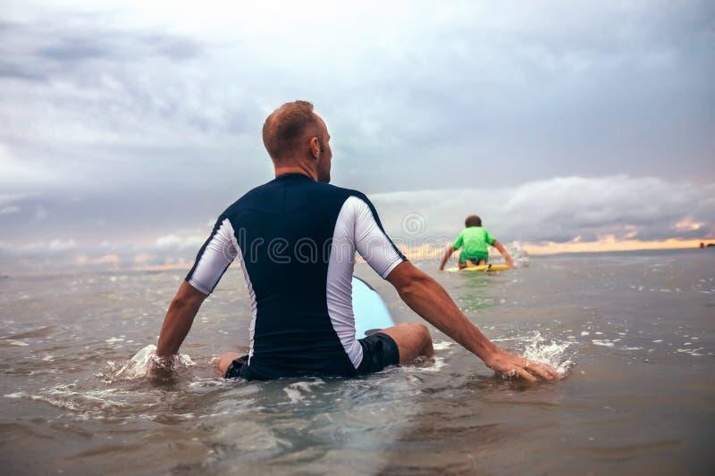 Os surfistas do pai e do filho superam ondas na linha da ressaca fotos de stock royalty free