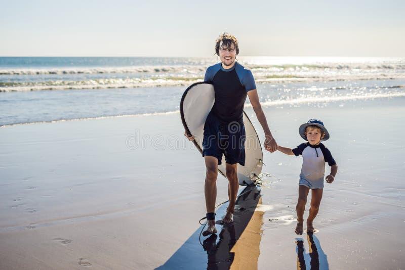 Os surfistas do pai e do filho têm uma boa estadia na praia imagem de stock royalty free