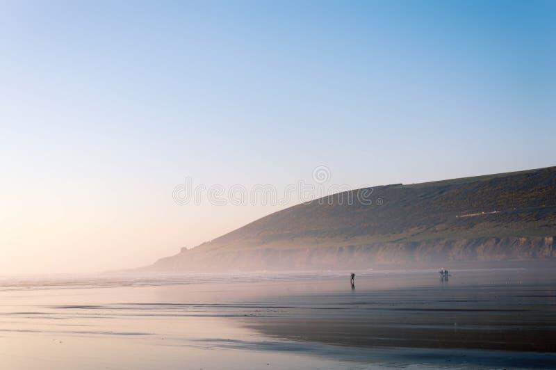 Os surfistas mostraram em silhueta o passeio na praia no por do sol em um dia morno 2019 de fevereiro Areias de Saunton, Devon, R foto de stock