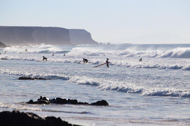 Os surfistas que surfam no EL Cotillo encalham, Fuerteventura, Ilhas Canárias, Espanha imagens de stock royalty free