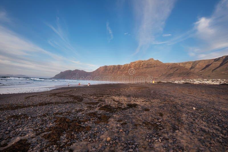 Os surfistas Unidentifiable em Famara famoso encalham em Lanzarote, Ilhas Canárias, Espanha fotos de stock royalty free