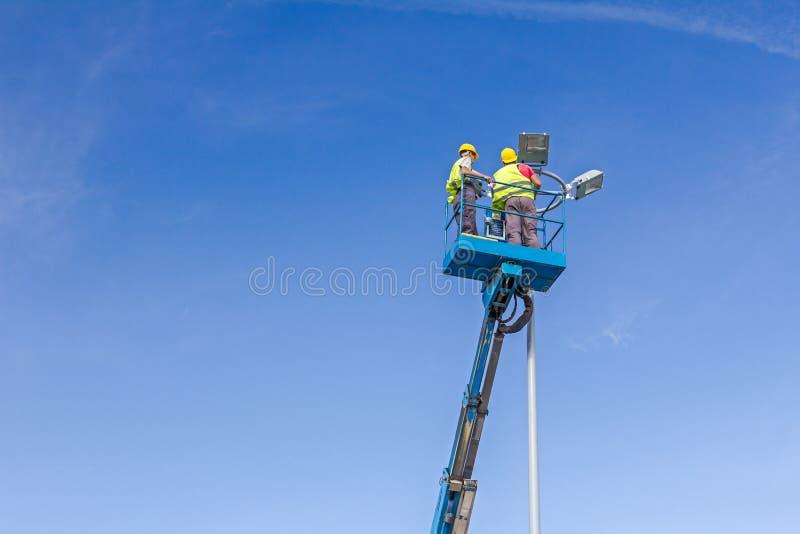 Os técnicos estão trabalhando em uma cubeta altamente acima em uma torre do projetor foto de stock royalty free