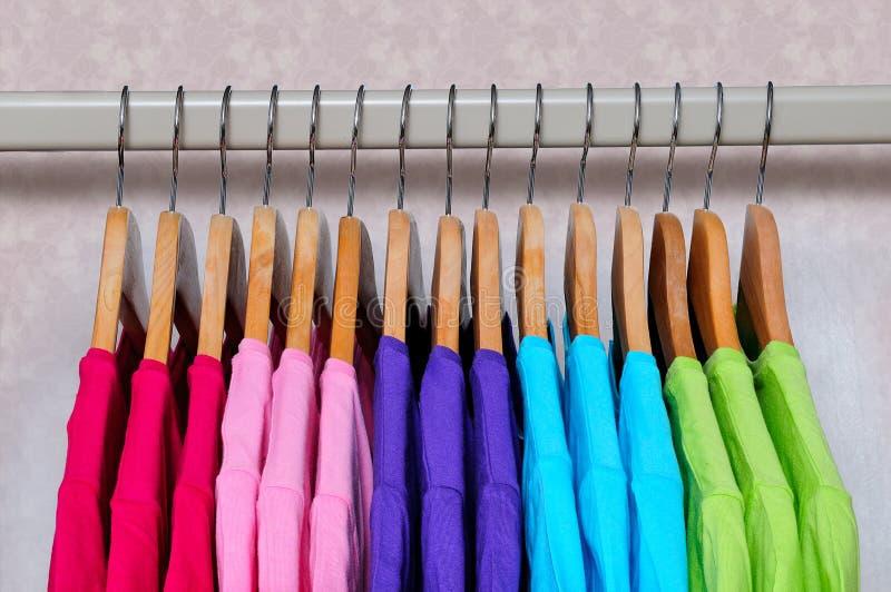 Os t-shirt coloridos das mulheres que penduram em ganchos de madeira fotos de stock royalty free