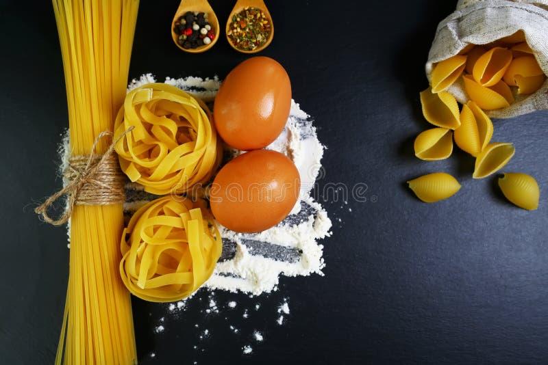 Os tagliatelle da massa, os espaguetes, os alimentos italianos conceito e o menu projetam, especiarias em colheres de madeira, sh imagens de stock